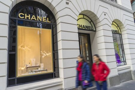 haute couture: Melbourne, Australia - August 16, 2015: Shoppers walking pass Chanel store in Melbourne. Chanel is a high fashion house specialising in haute couture, luxury goods and fashion accessories.