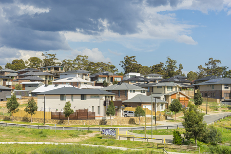 rows: Melbourne, Australia - October 11, 2015: Row of new, modern suburban houses on the hill in Melbourne with trees during daytime.