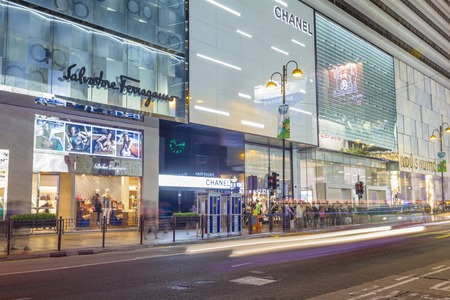 hong kong street: Hong Kong, China - June 13, 2015: Communters or shoppers waiting to cross the Canton Road with luxury brand stores in Hong Kong at night.