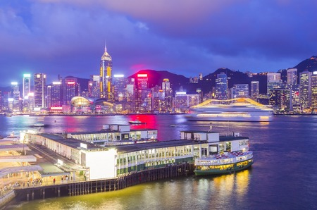 hong kong night: Star Ferry Pier at Tsim Sha Tsui with skyline of Hong Kong in the background at twilight