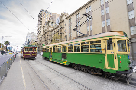 public transport: Melbourne, Australia - September 18, 2015: View of people in the vintage green and yellow tram plus the City Circle, the tourist tram on the street in Melbourne.