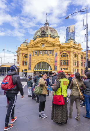 disadvantaged: Melbourne, Australia - September 9, 2015: A vendor selling The Big Issue magazine, independent magazine sold by disadvantaged people, to a woman near the Flinders Street Station in Melbourne.