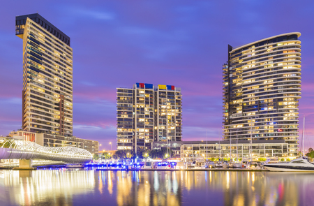 modern residential construction: Melbourne, Australia - November 3, 2015: View of modern residential buildings, Webb Bridge and marina with reflection in Docklands, Melbourne at twilight.