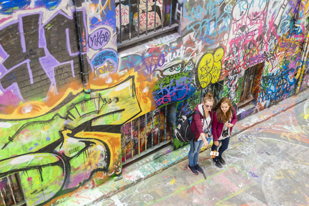 one lane: Melbourne, Australia - November 14, 2015: Two young, female tourists taking photos with smartphone selfie stick in Hosier Lane, Melbourne. Hosier Lane is one of the citys best street art locations.