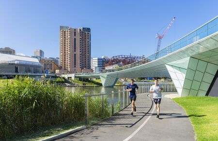 adelaide: Adelaide, Australia - November 27, 2015: Two men doing exercise in the Riverbank Precinct of Adelaide in South Australia with skyline in the background during daytime.