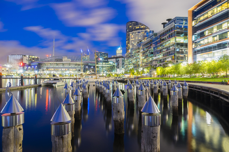Melbourne, Australia - November 13, 2015: View of bollards, modern buildings, apartments and Etihad Stadium in Victoria Harbour Promenade in Docklands, Melbourne at night. Editorial