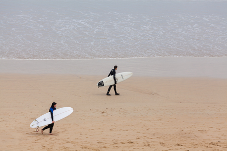 Victoria, Australia - November 22, 2015: View of two surfers at the beach in Torquay, along the Great Ocean Road, during daytime. Editorial