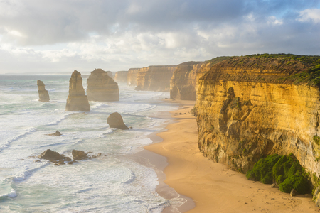 apostles: View of Twelve Apostles, waves and the beach in Great Ocean Road in Victoria, Australia during sunset Stock Photo
