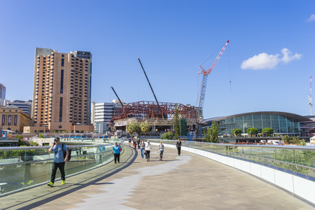 urban redevelopment: Adelaide, Australia - November 27, 2015: People walking along the footbridge, that links the Riverbank Precinct of Adelaide and  the Adelaide Oval, in South Australia. Editorial