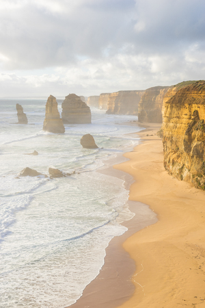 View of Twelve Apostles, waves and the beach in Great Ocean Road in Victoria, Australia during sunset Stock Photo