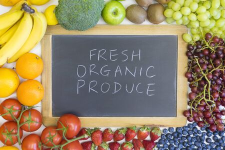 Black chalkboard for fresh, organic produce with food around it. Blank background for copy space