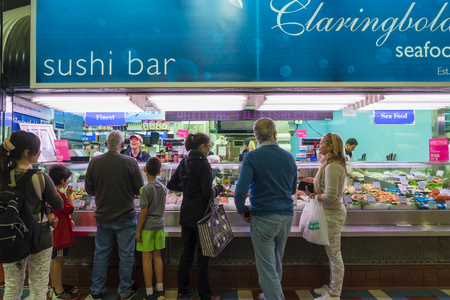 Melbourne, Australia - September 12, 2015: Customers queuing up to buy seafood from a shop assistant in a seafood store in Prahran Market, a iconic produce market, in Melbourne.