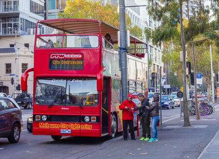 tourists stop: Melbourne, Australia - April 30, 2015: Two tourists asking a bus driver for information outside a sightseeing open top double decker bus stop in the city of Melbourne.