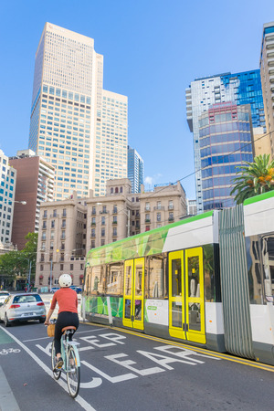 Melbourne, Australia - May 1, 2016: View of cyclist, cars and tram  with modern and historical buildings as background in Melbourne during daytime.