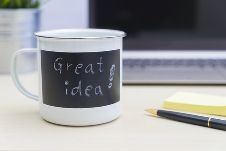 Great idea words on coffee mug with computer, pen, sticky notes and a potted plant on table
