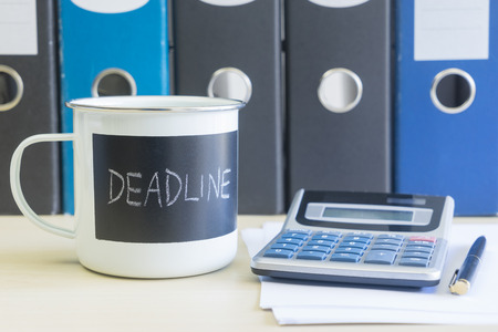 Meet your deadline words on coffee mug with calculator, pen, papers and some document box files on table