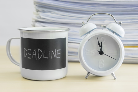 Meet your deadline words on coffee mug with alarm clock and stack of papers on table