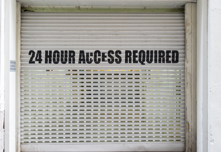 Front view of car park roller shutter with 24 hour access required wordings Stock Photo