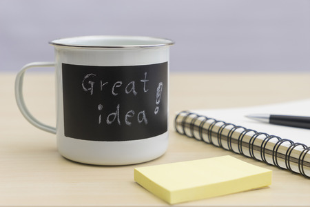 Great idea words on coffee mug with notepad, pen and sticky notes on table Stock Photo