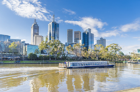 Melbourne, Australia - August 15, 2015: View of people taking a river cruise on Yarra River with Melbourne skyline in the background during daytime.