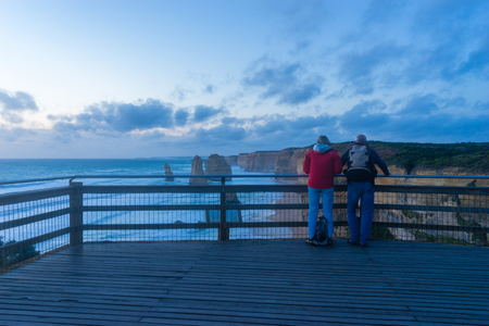 Victoria, Australia - November 24, 2015: View of two elderly tourists on the viewing platform of Twelve Apostles in Great Ocean Road in Victoria, Australia during sunset.