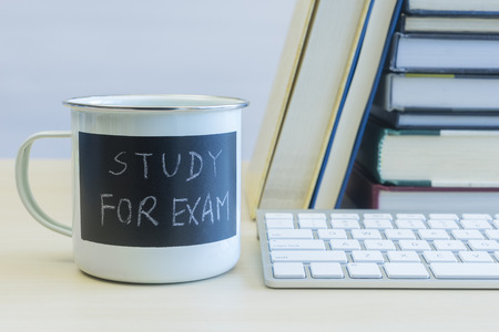 Study for exam words on coffee mug with keyboard and stack of books on table
