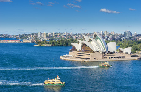 Aerial view of Sydney Harbour with ferries and cruises passing by Sydney Opera House during the daytime