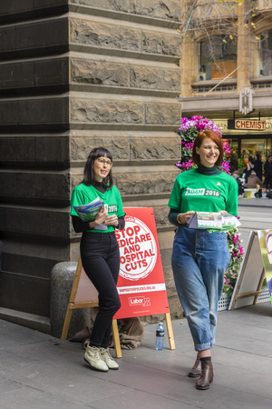 Melbourne, Australia - July 2, 2016: View of two volunteers from the Australian Greens party waiting to hand out pamphlets at Melbourne Town Hall to voters.