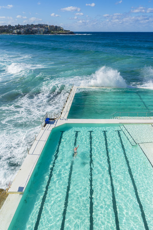 View of a man swimming in the outdoor pool at Bondi Beach and houses in a distance during daytime Stock Photo - 61880073