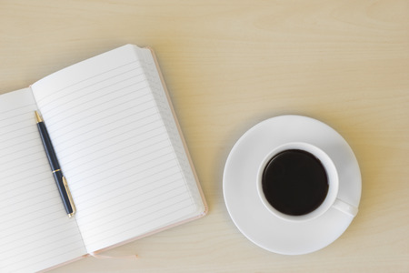 Top view of cup of coffee, blank notebook and pen on wooden table