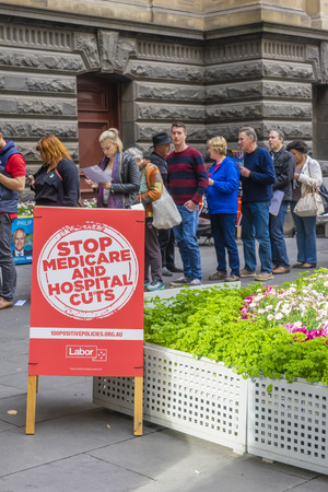encuestando: Melbourne, Australia - 2 de julio de, 2016: Vista del cartel electoral del partido y electores haciendo cola en el Ayuntamiento de Melbourne en el día de la votación del Trabajo de voto para la elección federal.