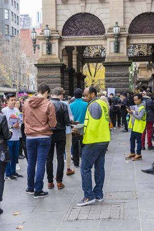 encuestando: Melbourne, Australia - 2 de julio de, 2016: Vista de electores haciendo cola en el Ayuntamiento de Melbourne en el día de la votación de voto para la elección federal, mientras que los voluntarios repartiendo panfletos.