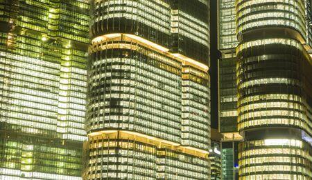 Close-up shot of exterior of modern skyscrapers illuminated at night