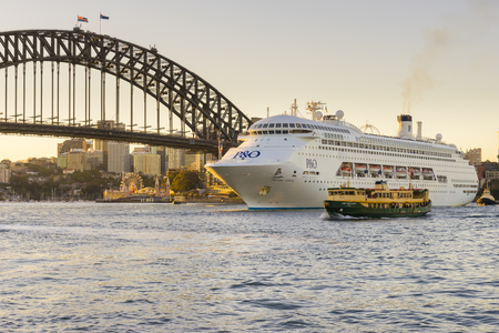 Sydney, Australia - June 25, 2016: View of luxury cruise ship and ferry near Harbour Bridge in Sydney at sunset with Luna Park and modern buildings in a distance. Editorial