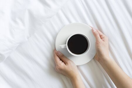 Top shot of woman hands holding a cup of hot coffee in bed concept