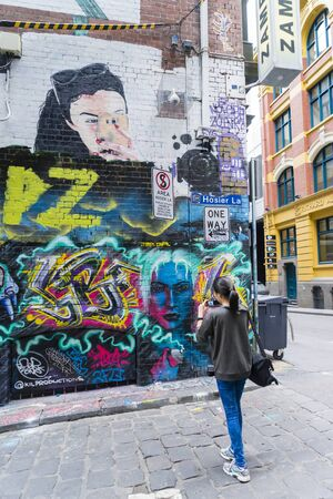 Melbourne, Australia - July 2, 2016: Tourist taking photos with camera in Hosier Lane, Melbourne. Hosier Lane is one of the citys best street art locations.
