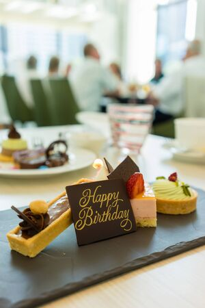 Different cakes on stylish plate with happy birthday wordings on a piece of chocolate in a cafe Stock Photo