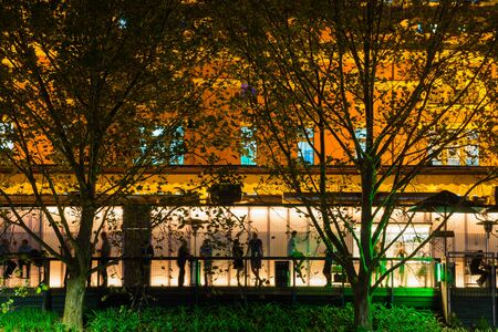 View of blurred people in a cafe at night with trees