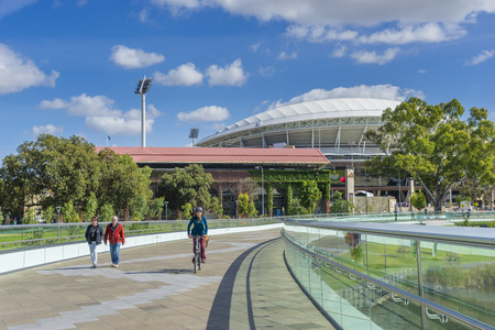adelaide: Adelaide, Australia - November 27, 2015: People walking and cycling along the footbridge, that links the Riverbank Precinct of Adelaide and  the Adelaide Oval, in South Australia.