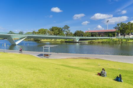 Adelaide, Australia - November 27, 2015: View of footbridge with people sitting on the grass enjoying the view of the riverbank of Adelaide city in Australia during daytime