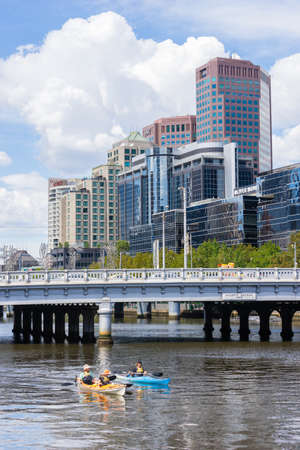 Melbourne, Australia - March 17, 2016: View of tourists on kayak tour along the Yarra River with cityscape of Melbourne as background. Kayaking is a new and fun way to see Melbourne. Editorial