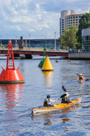 Melbourne, Australia - March 17, 2016: View of tourists on kayak tour along the Yarra River in Melbourne during daytime. Kayaking is a new and fun way to see Melbourne.