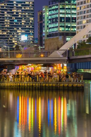 Melbourne, Australia - March 17, 2016: People having drinks in floating bar under the Yarra Pedestrian Footbridge with skyscrapers behind it in Melbourne at night.