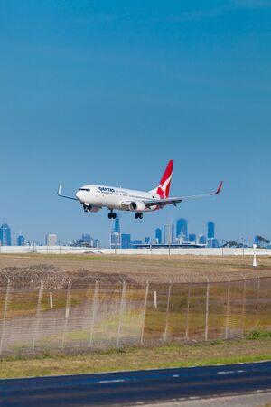 aircraft landing: Melbourne, Australia - April 26, 2016: View of Qantas aircraft landing at Melbourne Airport with modern buildings in the background during daytime.