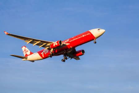 Melbourne, Australia - May 2, 2016: View of AirAsia aircraft approaching to landing at Melbourne Airport during sunrise. AirAsia is well-known Malaysian low-cost airline.
