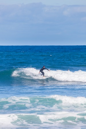 Victoria, Australia - March 25, 2016: View of surfer riding on waves at a beach in Torquay, along the Great Ocean Road, during daytime. Surfing is very popular among Australians. Editorial