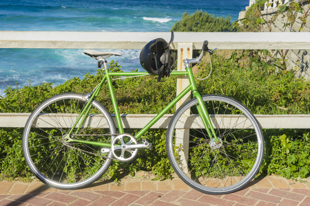 Fixed-gear bicycle in green and black helmet lean on the wooden fence with the sea and plants as background Stock Photo - 62816380