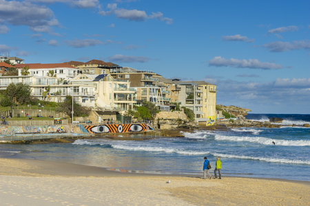 Sydney, Australia - June 25, 2016: View of people walking along the beach and modern apartments at Bondi Beach during daytime. Bondi Beach is one of the most famous beaches in Australia.