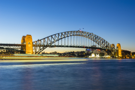 Sydney, Australia - June 25, 2016: View of Sydney Harbour Bridge at night with ship in motion blur and Luna Park and modern buildings in a distance at twilight.