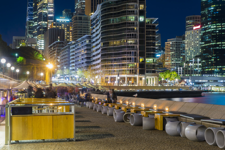 View of waterfront, outdoor cafe with people and illuminated, modern buildings at night